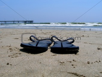Flipflops on wet sandy beach