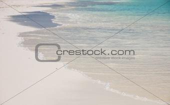 waves splashing on a white sand beach