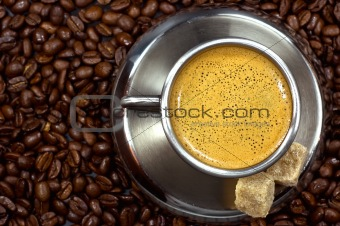 cup of coffee in a pile of coffee beans