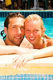 attractive young couple relaxing by the pool