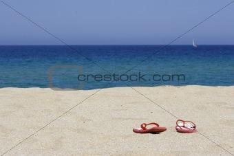 flip flops on empty sandy beach, corsica
