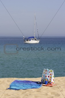 beach towel and bag with yacht in background, corsica, france