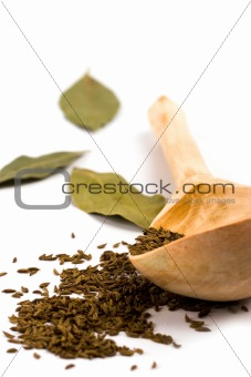 cumin on wooden spoon and bay leaves