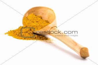yellow turmeric on wooden spoon