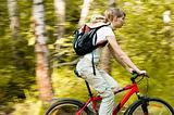 young woman with bicycle in forest