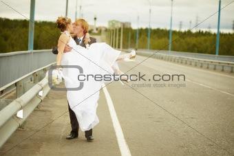 Groom carries his bride in his arms on bridge