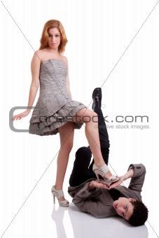 beautiful young woman stepping on a young man, isolated on white, studio shot