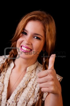 Young pretty women with thumb raised as a sign of success, thumbs up, isolated on black, studio shot