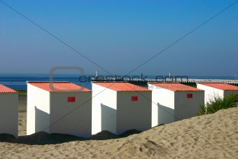 Close Up Beach Cabins with pier in background