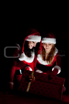 two woman in Santa costume opening christmas gift.