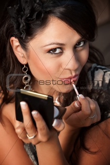 Beautiful Latina Woman with Compact Applying Lip Gloss