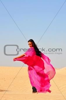 Beautiful young woman  dancing in arabic desert