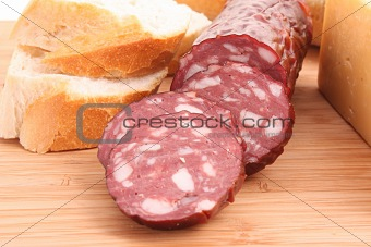 Sausage and bread on wooden surface