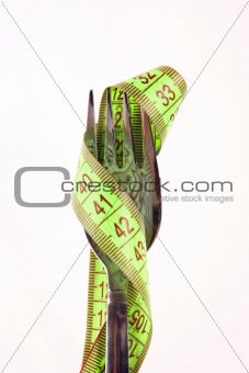 Green measuring tape on the fork isolated on white