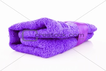 Folded purple towel with the band isolated on white