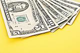 Few dollar banknotes on yellow background