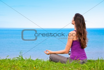 Beautiful young woman sitting meditating with a view of the ocean