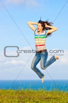 Beautiful young woman jumping up in the air laughing