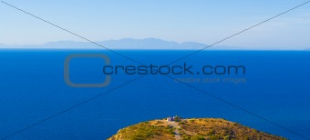 Cape, a lone house, the sea and the mountains in the distance. Rhodos. Greece
