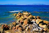 Stones on the Aegean coast and the mountains far away