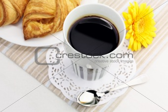 A cup of black coffee and croissants