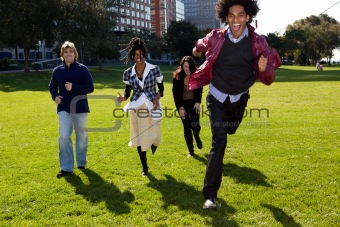 Four People Running Through an Urban Park