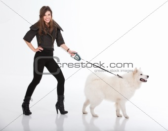 young woman walking a white dog viewed from a side