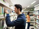 guy taking book from shelf in library