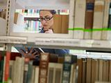 woman choosing book in library