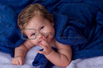 Beautiful baby under blue towel