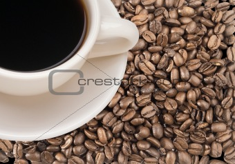 Freshly brewed coffee over dark roasted coffee beans