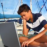teenager on boat with laptop computer