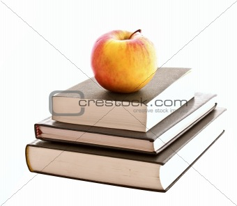 Three books and apple isolated on white