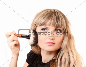 beautiful young woman applying makeup with brush