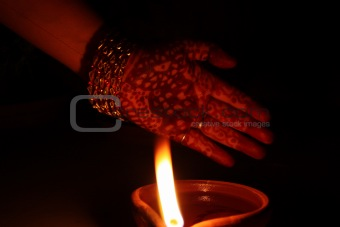 Hand with Mehndi (henna) in front of a lamp