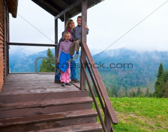Family on wooden mountain cottage porch