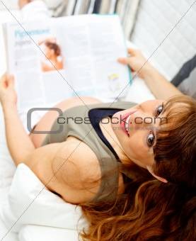 Smiling beautiful pregnant female reading magazine while sitting on sofa.