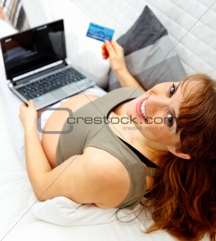 Smiling beautiful pregnant woman on sofa with the laptop and a  credit card.