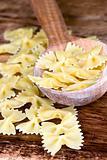 uncooked pasta in wooden spoon