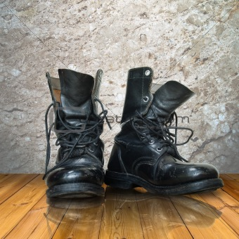 old black boot on wood floor