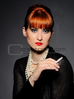 Beautiful retro woman with red lips holding cigarette and smokin