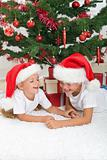 Laughing kids in front of the christmas tree