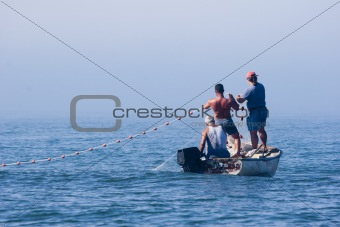 fishermen in their boat pulling nets