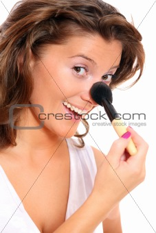 Cute woman putting on her makeup