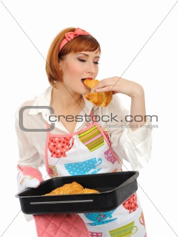 Beautiful cooking woman in apron eating fresh made croissant