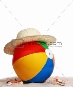 beach ball and hat on beach sand