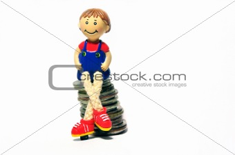 toy boy sitting on a hill of coins