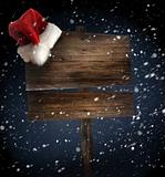 Weathered wooden sign with Santa hat
