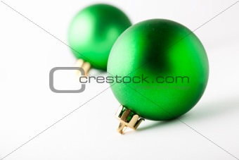 Green Christmas baubles on white