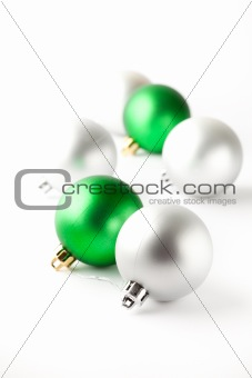 Green and silver Christmas baubles on white